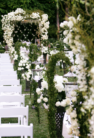 the-aisle-of-a-garden-ceremony-was-decorated-with-greenery-and-white-roses