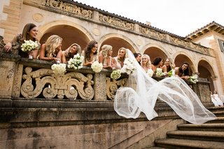 brides-veil-billowing-while-she-and-bridesmaids-lean-over-railing