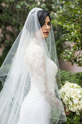 bride-holding-white-bouquet-in-sweetheart-neckline-wedding-dress-with-long-sleeve-illusion-bolero