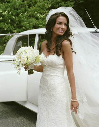 bride-with-bouquet-in-front-of-vintage-car
