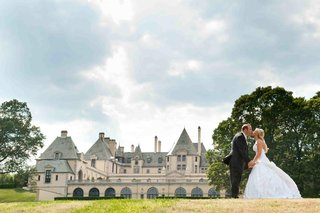 bride-and-groom-kiss-in-front-of-oheka-castle
