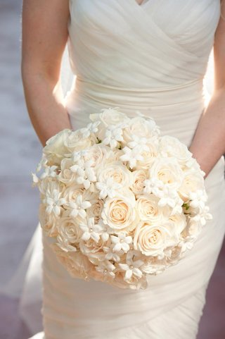 bride-holding-round-white-bouquet-with-roses-and-pearls