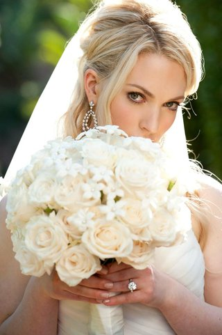 blonde-bride-holding-bouquet-in-front-of-face-with-natural-makeup