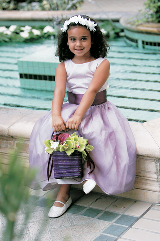 flower-girl-wearing-light-purple-dress-with-a-dark-purple-sash-holding-a-basket-of-flowers