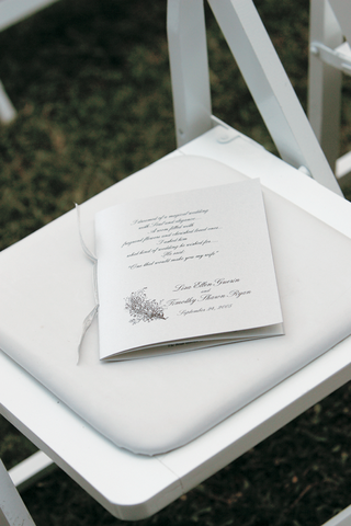 white-wedding-program-with-a-silver-ribbon-and-script-font