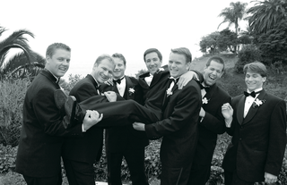 groomsmen-in-tuxedos-pick-up-groom