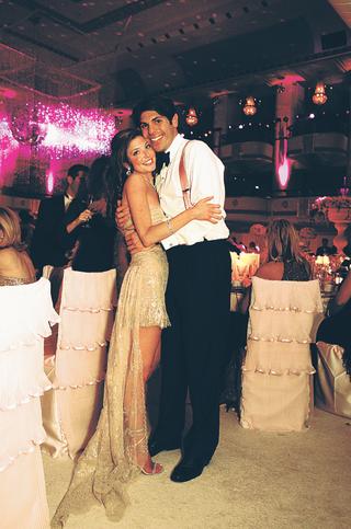 groom-hugs-bride-wearing-short-tan-dress-at-reception