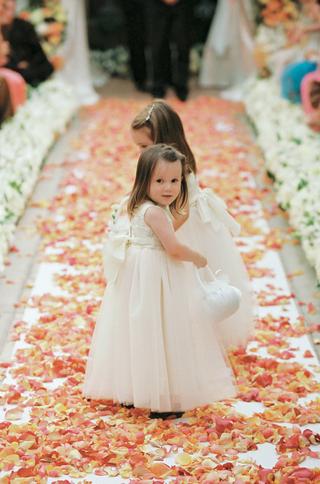 two-flower-girls-walk-down-flower-petal-aisle