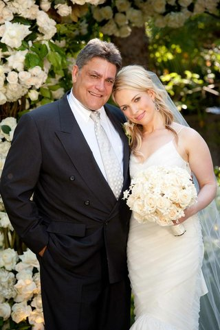 bride-smiles-with-father-of-bride-in-front-of-roses