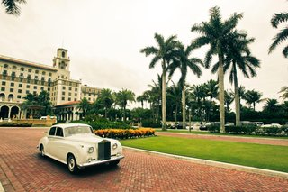vintage-white-car-driving-in-front-of-the-breakers-resort