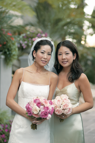 jenny-yoo-and-her-sister-hold-bouquets-of-pink-roses-and-peonies