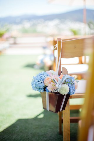 bronze-box-filled-with-florals-hanging-from-chair