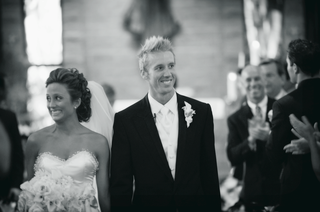 black-and-white-photo-of-couple-walking-up-aisle