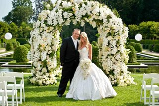 bride-in-a-strapless-pnina-tornai-gown-with-groom-in-a-black-tuxedo-and-white-bow-tie-at-floral-arch