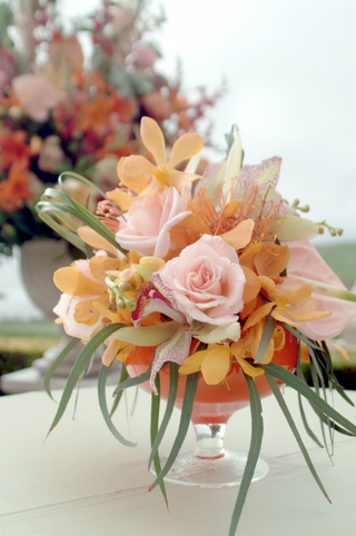 wedding-ceremony-arrangement-of-pink-and-orange-flowers-with-greenery-in-a-cocktail-glass