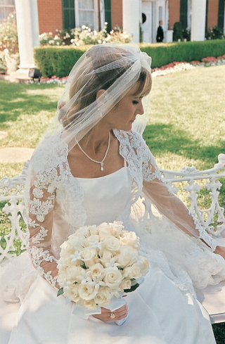 bride-wearing-dress-with-lace-sleeves-carrying-rose-bouquet