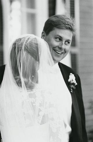 groom-smiles-at-bride-wearing-wedding-veil