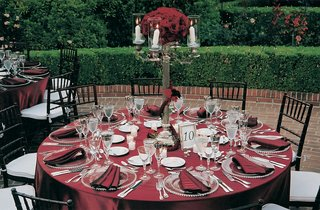round-table-with-red-linens-and-black-chairs
