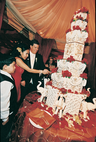 bride-and-groom-cut-seven-tier-white-gold-and-red-cake