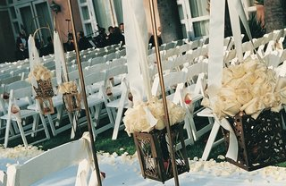 white-ceremony-chairs-and-aisle-runner-with-white-roses