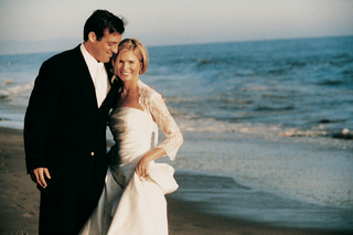 groom-and-bride-smile-on-sand-in-front-of-ocean