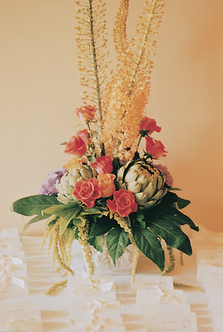 white-table-cards-with-bows-below-towering-flower-arrangement