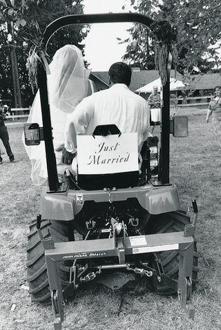 black-and-white-photo-of-newlyweds-driving-off-in-a-tractor