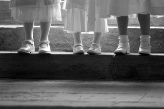 black-and-white-image-of-three-flower-girls-on-step-with-just-shoes-and-socks-showing