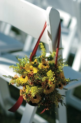 autumn-flowers-and-foliage-hanging-from-white-ceremony-chair