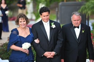 parents-in-formal-attire-walking-groom-down-aisle