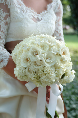 bride-holds-bouquet-with-garden-rose-hydrangea-and-stephanotis-flowers