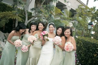 jenny-yoo-and-bridesmaids-in-strapless-pastel-green-dresses-carrying-light-pink-bouquets