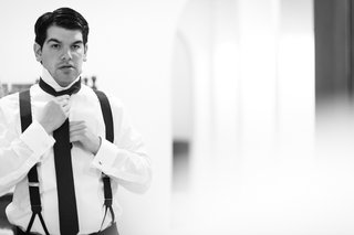 black-and-white-photo-of-man-putting-on-tie