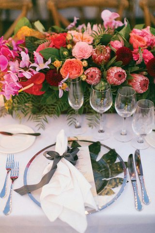 wedding-reception-tropical-place-setting-protea-rose-orchid-centerpiece-palm-under-ribbon