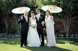 wedding-couple-with-parents-holding-parasols