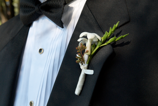 tiny-white-blossom-and-green-stem-boutonniere