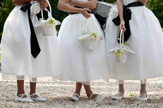 flower-girls-in-white-dresses-with-black-sashes-and-ballet-slippers-and-flats-carry-white-baskets
