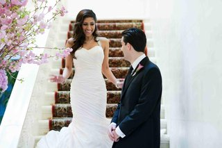 groom-looks-at-bride-as-she-comes-down-stairs