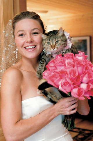 bride-holding-bouquet-and-kitten-with-flower-collar