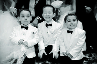 black-and-white-photo-of-three-boys-wearing-white-tuxedo-jackets-and-bow-ties-at-wedding