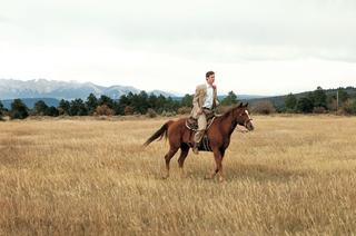 groom-riding-brown-horse-at-colorado-ranch-wedding-venue
