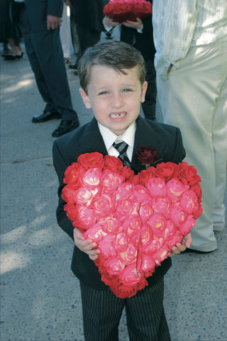 ring-bearer-holding-red-and-pink-heart-shaped-ring-pillow