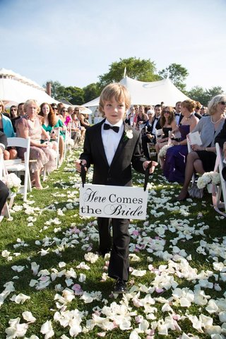 ring-bearer-holds-here-comes-the-bride-signage