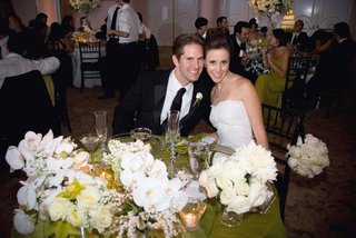 bride-and-groom-sit-at-wedding-reception-table