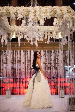 bride-stands-underneath-chuppah-in-white-dress-with-black-sash