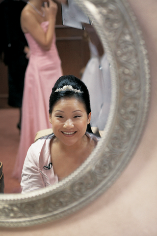 bride-with-updo-hairstyle-looking-in-mirror