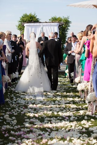 bride-escorted-down-aisle-by-her-father-on-grass