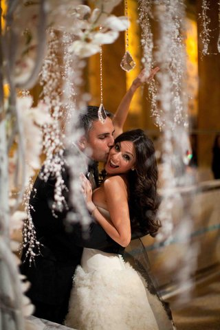 groom-hugs-and-kisses-bride-under-crystal-chuppah