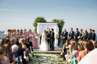 bride-and-groom-at-white-ceremony-structure-on-coast