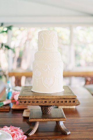 unique-cake-with-white-design-on-wood-pedestal